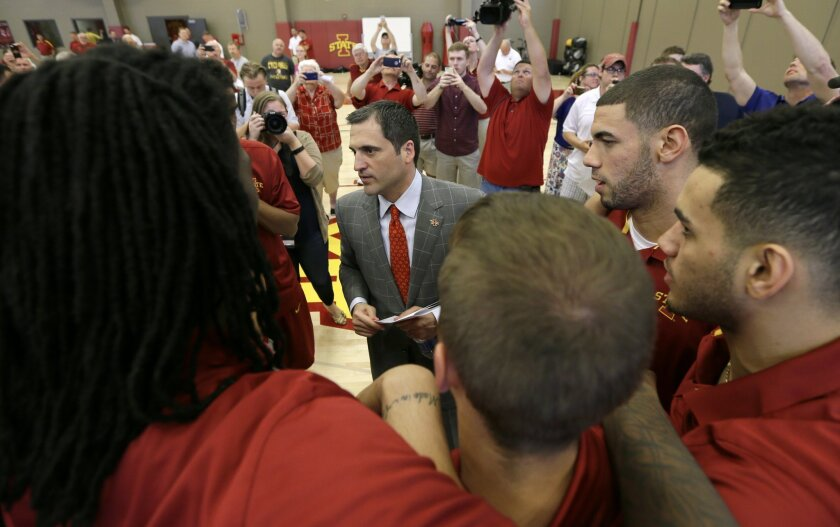 In this June 9, 2015, photo, new Iowa State men's basketball coach Steve Prohm, center, talks with senior Georges Niang, second from right, and his teammates following a news conference in Ames, Iowa. Prohm has inherited one of the nation's most talented rosters and perhaps the country's smartest p