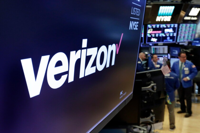 FILE - This April 23, 2018, file photo shows the logo for Verizon above a trading post on the floor of the New York Stock Exchange. Verizon's decision to join the growing boycott against Facebook and Twitter risks hurting the social media giants where it hurts most: their advertising revenue. Advertising accounts for nearly all Facebook's $70.7 billion annual revenue, and a similar share of Twitter's $3.46 billion. (AP Photo/Richard Drew, File)
