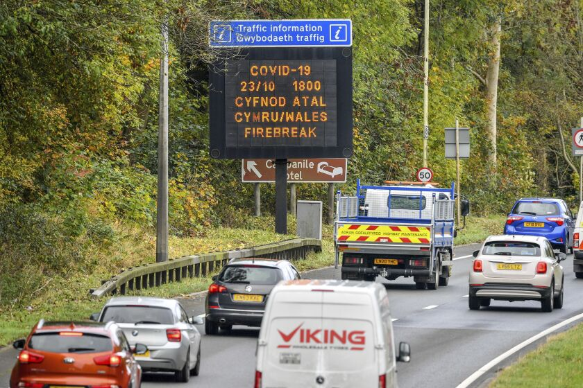"""A matrix sign on the A48(M) heading towards Cardiff informing motorists to Wales entering a """"firebreak"""" lockdown, Friday, Oct. 23, 2020. A police force in England says it will try to stop people from leaving Wales, which has started a 17-day lockdown to slow the spread of COVID-19. The Gloucestershire Constabulary says it will patrol routes from Wales and pull over drivers they believe are making long journeys. Travelers without a good excuse will be asked to turn around. (Ben Birchall/PA via AP)"""
