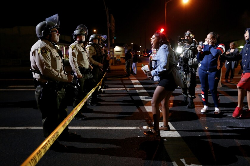 A woman confronts L.A. County Sheriff's deputies blocking the street after a vigil was held for Carnell Snell Jr., an 18-year-old fatally shot by LAPD officers Saturday following a vehicle pursuit.