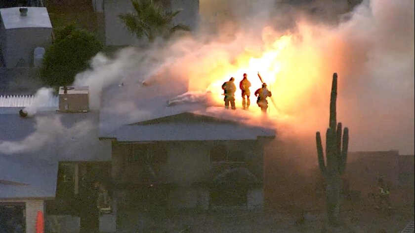 This image made from video provided by KNXV ABC-15 Arizona shows firefighters atop a house engulfed in flames in Phoenix on Tuesday, Feb. 23, 2016. Police and firefighters braved bullets and flames as they responded to the fatal shooting and house fire. (KNXV ABC-15.com via AP)