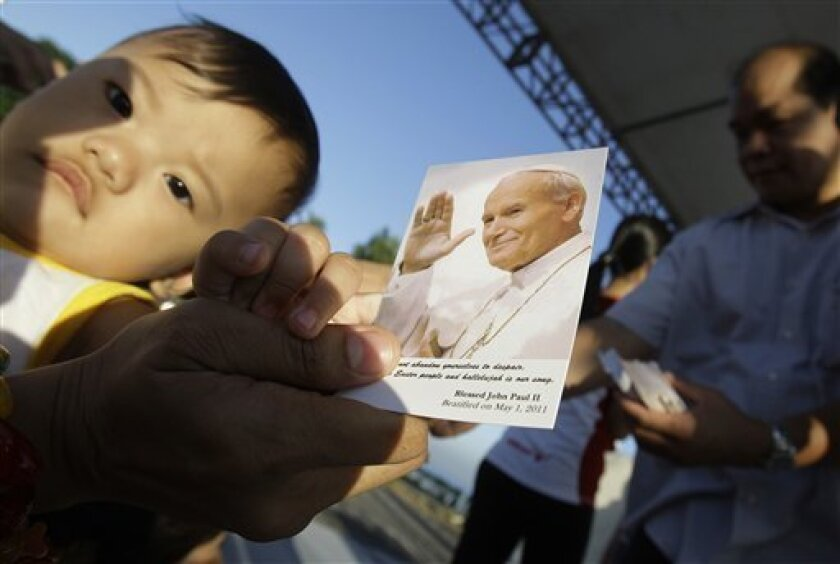 A Filipino devotee and her baby receive a picture of Pope John Paul II as they celebrate his beatification at Manila, Philippines on Sunday May 1, 2011. Filipinos who adored John Paul II celebrated his beatification with prayers and treasured mementos. The popular pontiff has a large following in this predominantly Roman Catholic nation. (AP Photo/Aaron Favila)