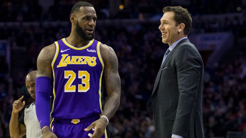 Los Angeles Lakers' head coach Luke Walton, right, talks things over with LeBron James, left, during