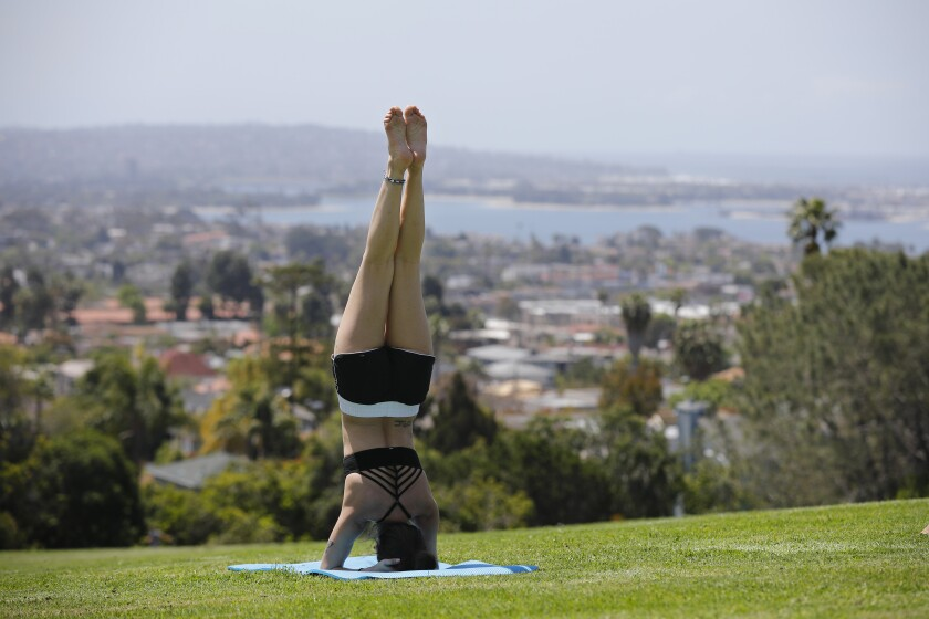 Mandy Delgado does a yoga headstand at Kate Sessions Park in Pacific Beach on April 21, 2020. Most San Diego parks and trails that were closed due to Covid-19 were reopened to the public Tuesday.