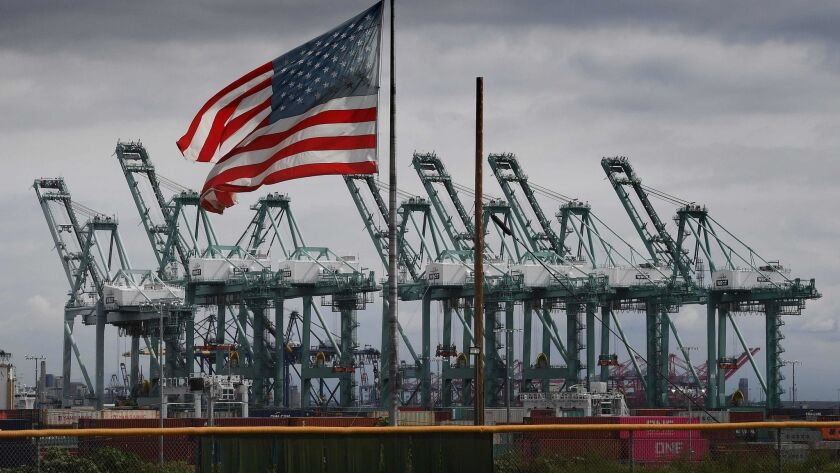 Flags fly over shipping cranes and containers in Long Beach, Calif. The skyrocketing U.S. trade deficit last year hit the highest level in a decade, a major setback for President Trump's global trade offensive.