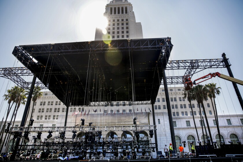 With Los Angeles City Hall in the background, crews work to set up equipment on a stage for this weekend's Made In America concert.