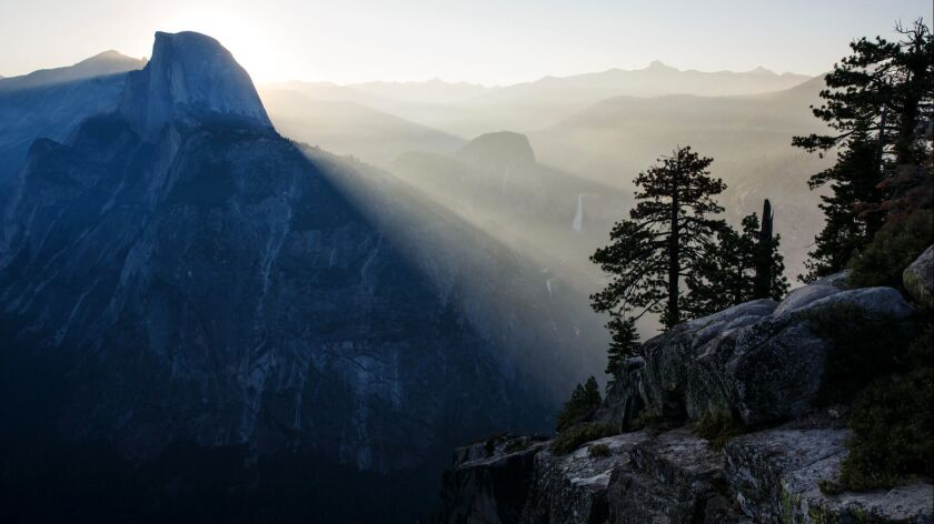 Visitors watch the sun rise behind Half-Dome, in Yosemite National Park, Calif.