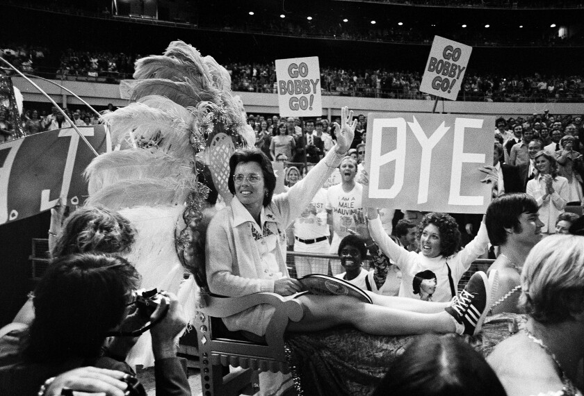 """Billie Jean King is carried on a litter into the Battle of the Sexes, with """"Go Bobby Go!"""" signs behind her."""