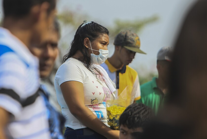 A woman in a surgical mask attends a funeral May 11 at a cemetery in Managua, Nicaragua.