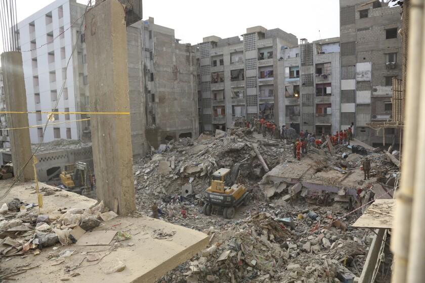 Pakistani troops, rescue workers and volunteers look for survivors amid the rubble of a collapsed building in Karachi, Pakistan, Monday, June 8, 2020. The multi-story residential building that was being expanded collapsed in a congested area of Karachi on Thursday. (AP Photo/Fareed Khan)
