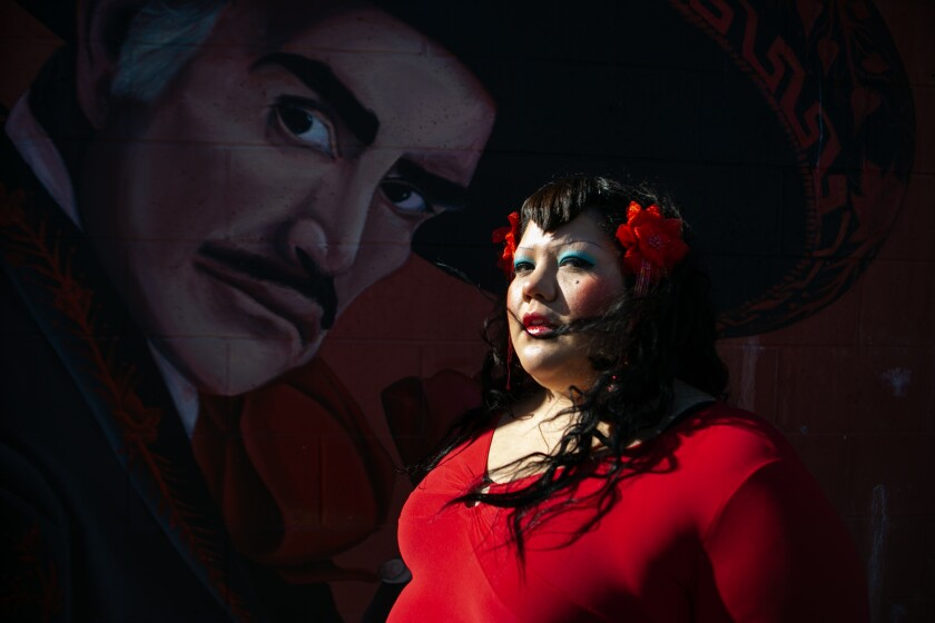 Gabriela Ruiz stands before a mural at Plaza del Valle market in Panorama City.