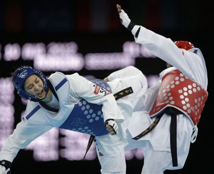 South Korea's Hwang Kyung-seon fights Ivory Coast's Ruth Gbagbi (in red) during their match in women's 67-kg taekwondo competition at the 2012 Summer Olympics, Friday, Aug. 10, 2012, in London. (AP Photo/Ng Han Guan)