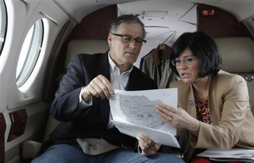 Washington Gov. Jay Inslee, left, looks at a map with Dept. of Ecology Director Maia Bellon, right, Wednesday, March 6, 2013, as they fly to Richland, Wash. to tour the Hanford Nuclear Reservation and meet with Dept. of Energy officials in order to learn more about tanks on the site that are leaking radioactive waste. (AP Photo/Ted S. Warren)