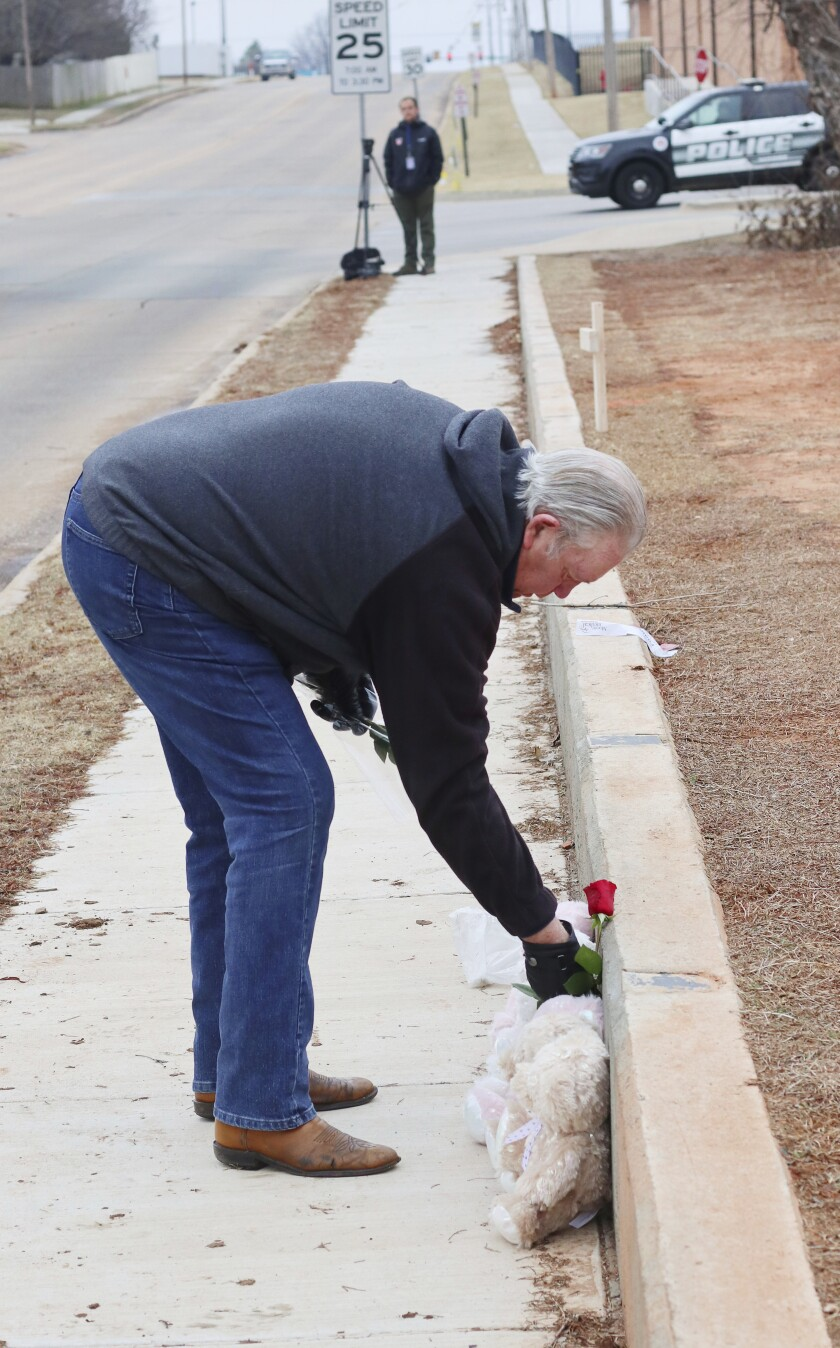 An unidentified man leaves a rose at the scene where makeshift memorials for Rachel Freeman, and others, at the location on Main Street Tuesday, Feb. 4, 2020, where Moore High School cross country runners were run over by a pickup truck driven by Max Leroy Townsend, 57, Monday, killing Freeman and Yuridia Martinez. (Doug Hoke/The Oklahoman via AP)