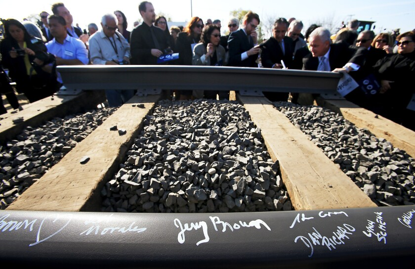 Guests sign a rail segment during a groundbreaking ceremony for a California bullet train station in Fresno on Jan. 6, 2015.