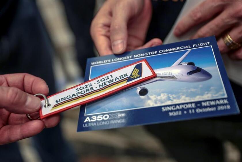 Imagen de un llavero y una postal conmemorativos del vuelo SQ22 de la aerolínea Singapore Airlines en el aeropuerto de Changi en Singapur, hoy, 11 de octubre de 2018. EFE