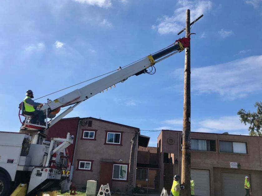 A San Diego Gas & Electric crew removes an above-ground utility pole in Sherman Heights in September 2019.