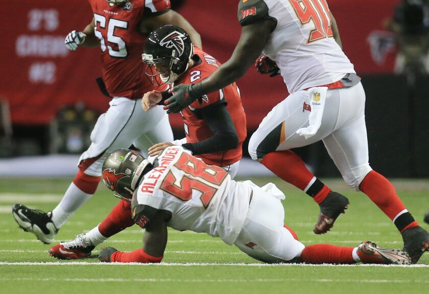 Atlanta Falcons quarterback Matt Ryan helps tackle Buccaneers linebacker Kwon Alexander after Alexander intercepted Ryan during the second quarter in a football game on Sunday, Nov. 1, 2015, in Atlanta. (Curtis Compton/Atlanta-Journal Constitution via AP) MARIETTA DAILY OUT, GWINNETT DAILY POST OUT