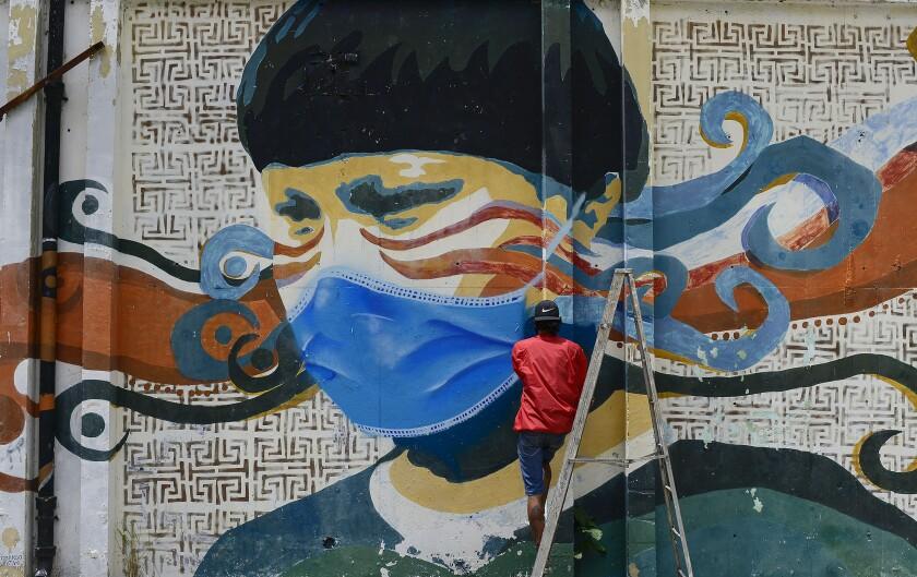 A street artist spray-paints a protective mask over an old mural in Caracas, Venezuela