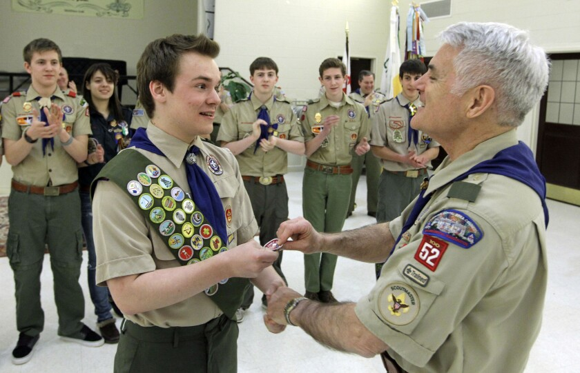 Pascal Tessier, left, receives his Eagle Scout badge from Troop 52 Scoutmaster Don Beckham on Monday in Chevy Chase, Md. Tessier became the first openly gay scout to reach the highest rank since a policy change to allow gay youth in the Boy Scouts of America.
