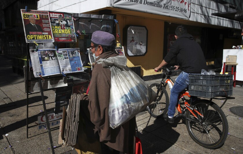 A man reads the front pages of newspapers