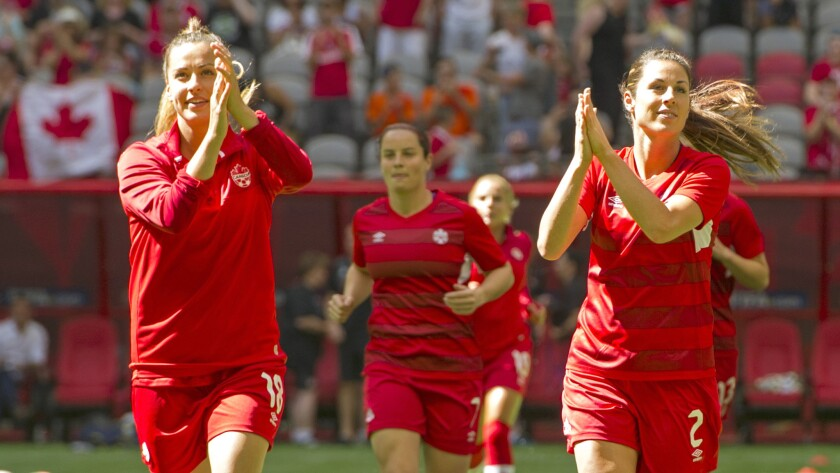 Canada's Selenia Iacchelli (18) and Emily Zurrer (2) acknowledge the fans as they take the field before a Women's World Cup quarterfinal against England on Saturday in Vancouver.