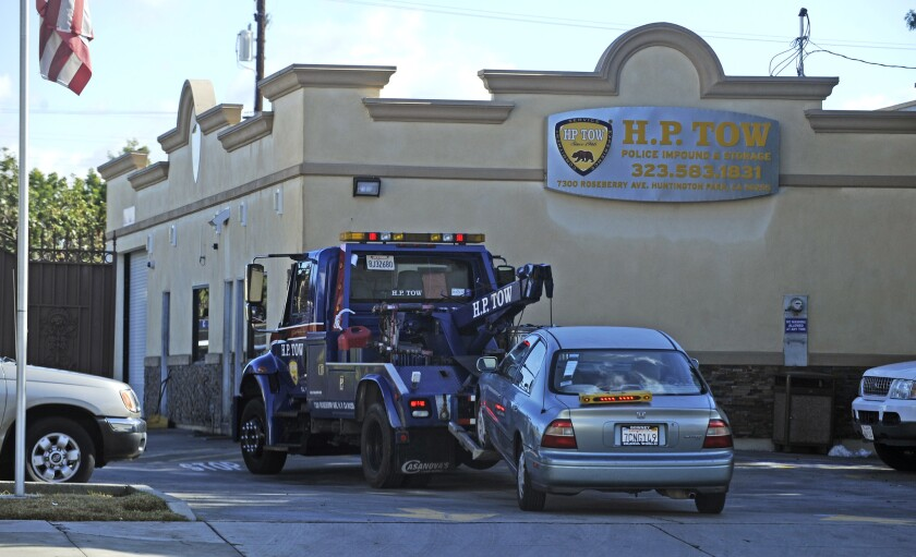 A car is towed into the lot at H.P. Tow in Huntington Park earlier this year. A federal grand jury has indicted one of the company's owners.