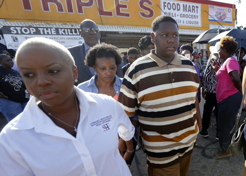 Cameron Sterling, center, son of Alton Sterling, who was killed by Baton Rouge police last Tuesday, leaves after speaking to the media outside the the Triple S Food Mart, where his father was killed,in Baton Rouge, La., Wednesday, July 13, 2016. Cameron called his father a good man and urged protesters not to resort to violence. (AP Photo/Gerald Herbert)