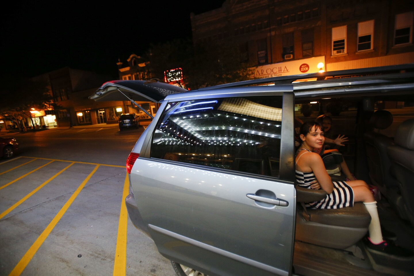 """Alaina Spaulding, 11, of Webster City prepares to leave the theater after seeing """"Mamma Mia 2"""" with her mother at the Webster Theater in Webster City, Iowa. Community members rallied around the theater to save it after it closed in 2013."""