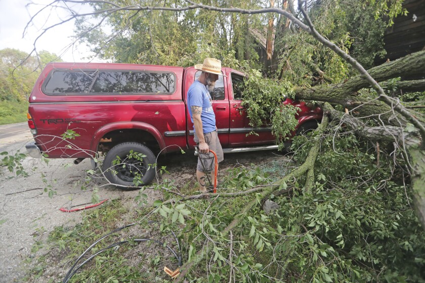 Adam Turley examina los daños sufridos por la camioneta de su padre delante de su casa en Concord Center Drive, en Concord, Wisconsin, el jueves, 29 de julio del 2021. Fuertes tormentas eléctricas causaron daños en Wisconsin, dejaron a decenas de miles de personas sin electricidad y provocaron advertencias de tornado. (Mike De Sisti/Milwaukee Journal-Sentinel vía AP)