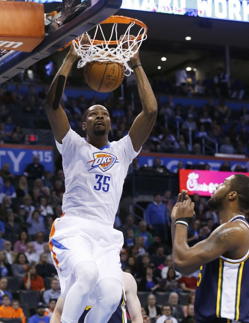 Oklahoma City Thunder forward Kevin Durant (35) dunks in front of Utah Jazz forward Derrick Favors, right, during the first quarter of an NBA basketball game in Oklahoma City, Thursday, March 24, 2016. (AP Photo/Sue Ogrocki)