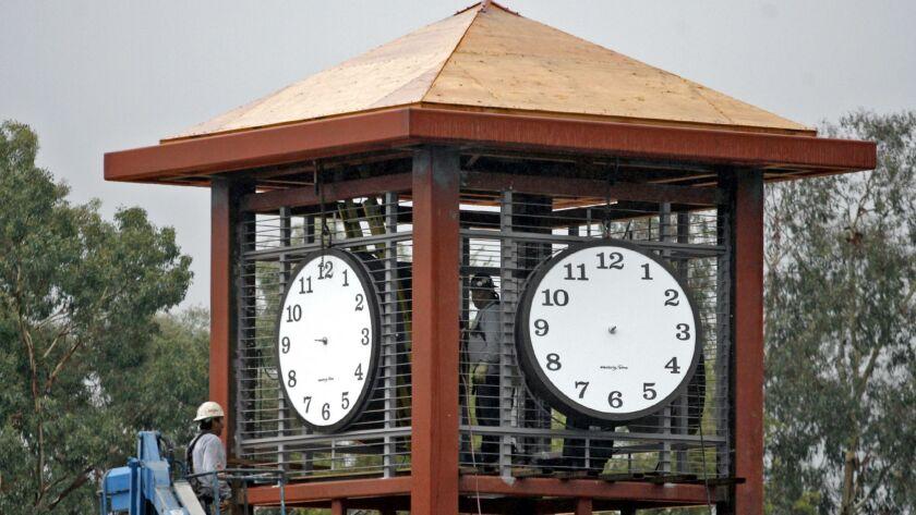 Amid falling rain, the new Flintridge Bookstore building on Foothill Blvd. got its clocks installed