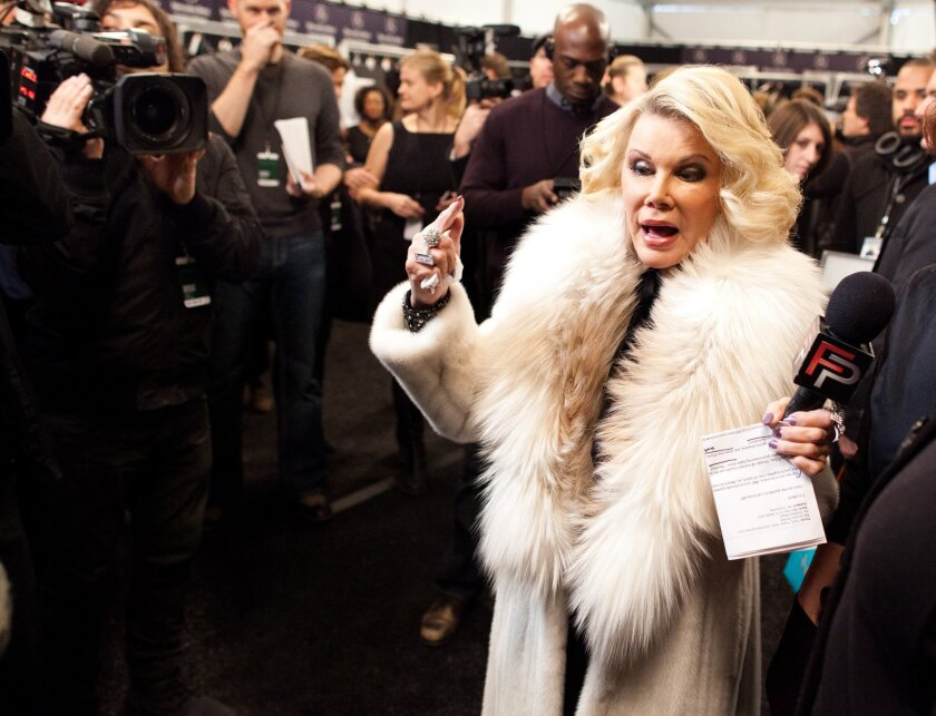 """In this Feb. 14, 2012 file photo, Joan Rivers tours backstage with her camera crew for E!'s """"Fashion Police,"""" before the Badgley Mischka show during Fashion Week in New York. Rivers died Thursday, Sept. 4, 2014. She was 81. (AP Photo/John Minchillo, File)"""
