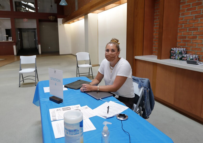 Marisa Fader of Bushard's Pharmacy welcomes people to their vaccine stations.