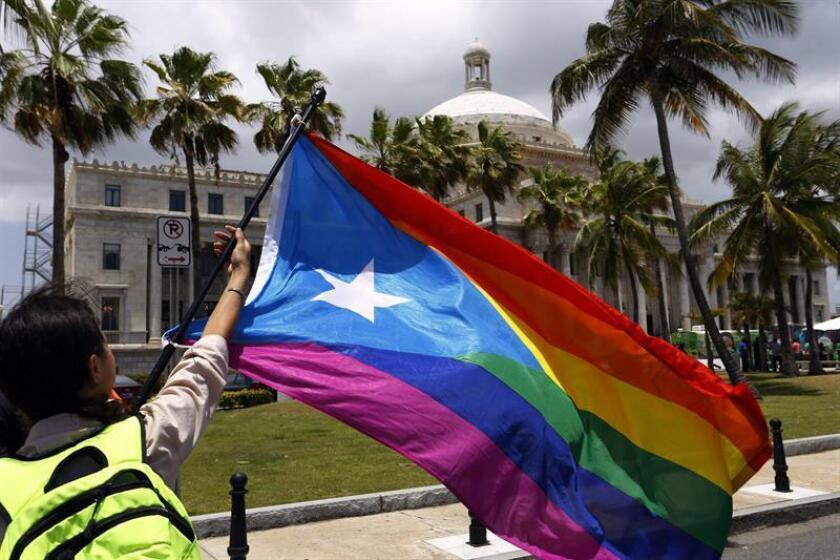 Una mujer ondea una bandera gay en San Juan (Puerto Rico). EFE/Archivo