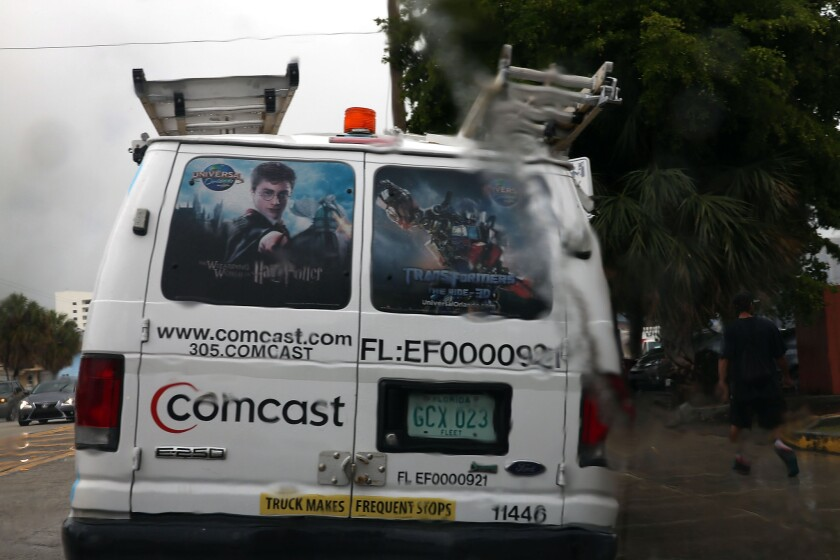 A Comcast service van is seen through a rain soaked windshield on Thursday in Miami.