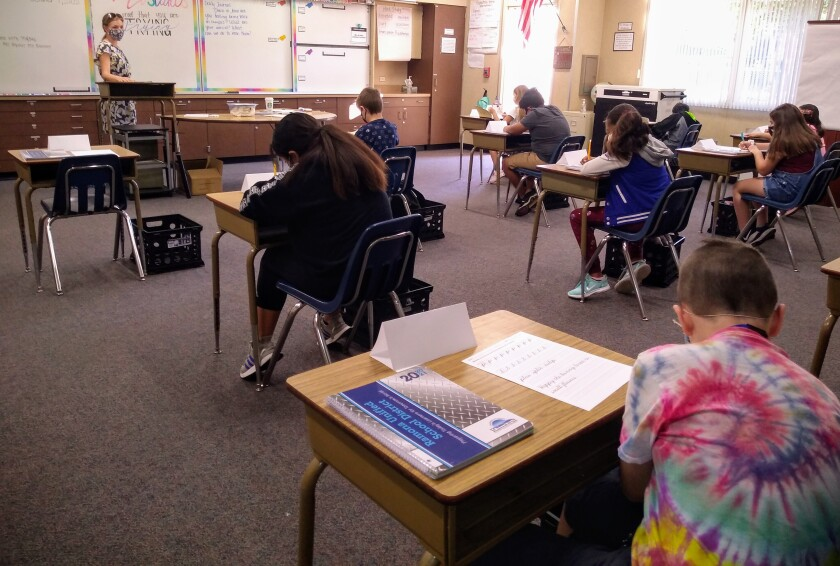 Inside a classroom, children sit at desks spaced apart. A teacher in a mask stands at the front of the class.
