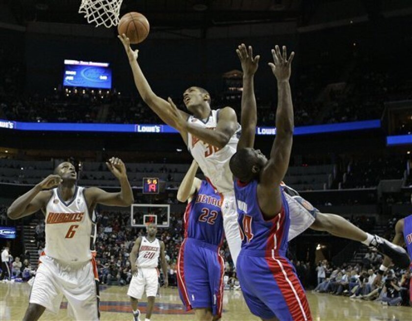Charlotte Bobcats forward Boris Diaw, top, of France, drives past Detroit Pistons forward Jason Maxiell (54) as Charlotte Bobcats center Nazr Mohammed (6) looks on during the first half of an NBA basketball game in Charlotte, N.C., Saturday, Dec. 13, 2008. (AP Photo/Chuck Burton)