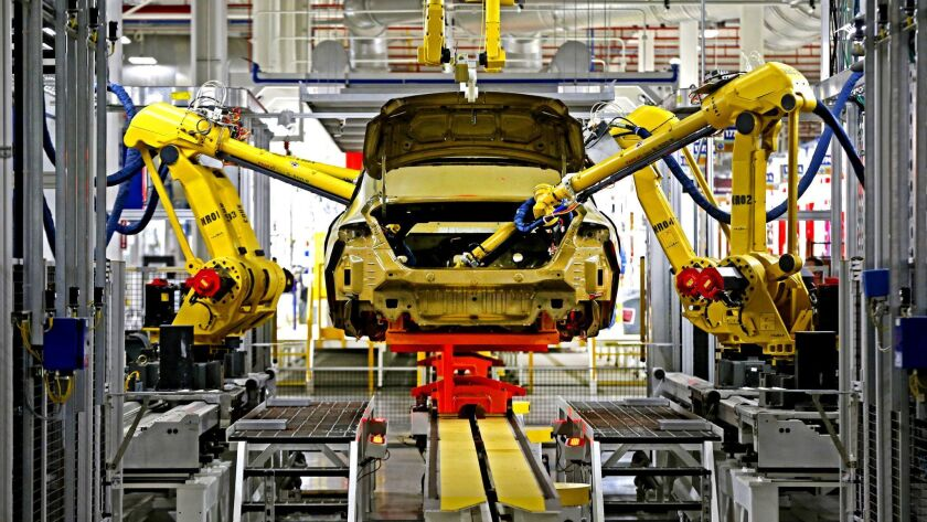 FILE - In this March 14, 2014 file photo, automated robots build a 2015 Chrysler 200 at the Sterling