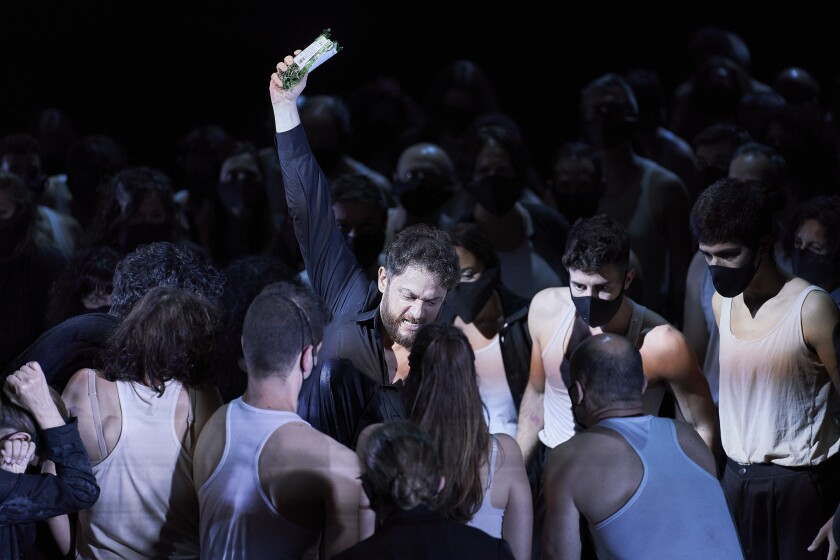"One of eight unmasked singers in ""Otello"" at Gran Teatre del Liceu in Barcelona, surrounded by masked chorus members"