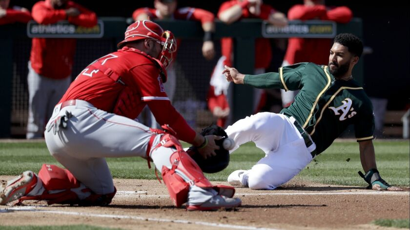 Oakland Athletics shortstop Marcus Semien, right, scores past Los Angeles Angels catcher Kevan Smith on a two-run double by Stephen Piscotty during the first inning of Tuesday's exhibition game.