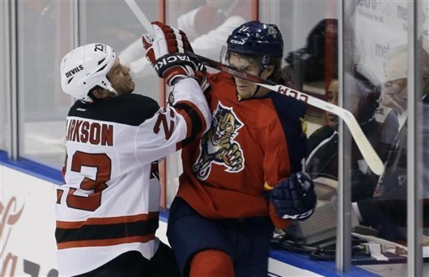 New Jersey Devils' David Clarkson (23) slams Florida Panthers' Jonathan Huberdeau (11) into the glass during the first period of a NHL hockey game in Sunrise, Fla., Saturday, March 30, 2013. (AP Photo/J Pat Carter)