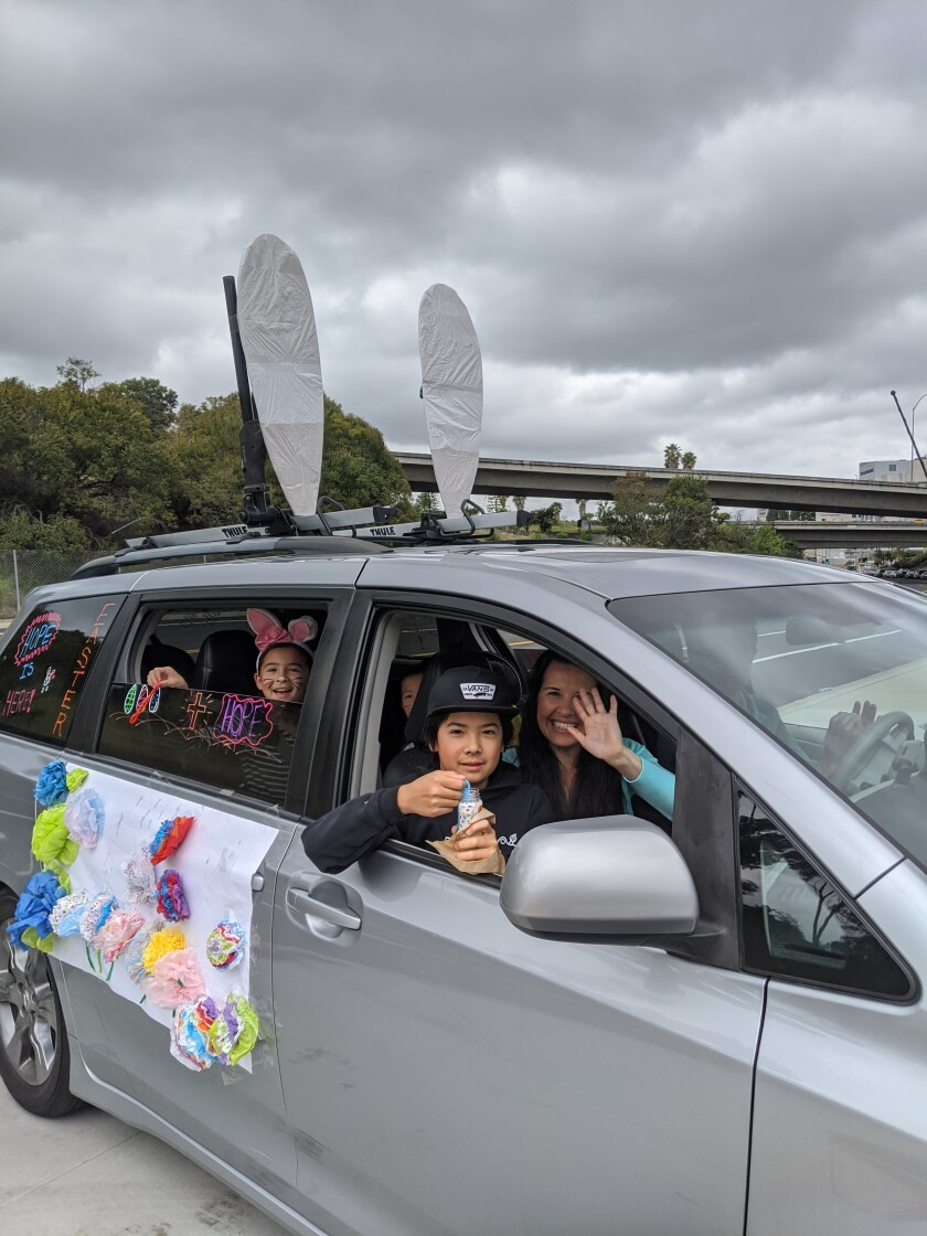 """Tira Wakayama and her family participate in the """"Caravan of Hope"""" Easter Sunday, April 12, 2020. Members of Grace Church drove to different nursing homes and hospitals to spread holiday cheer during the coronavirus pandemic."""