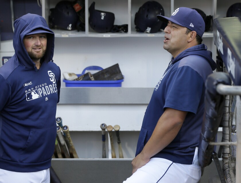 Padres interim manager Rod Barajas (right) enjoys a moment with relief pitcher Kirby Yates in the dugout before Saturday's game against the Arizona Diamondbacks.
