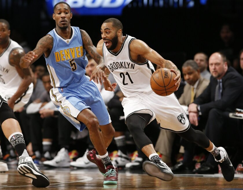 Brooklyn Nets guard Wayne Ellington (21) drives around Denver Nuggets forward Will Barton (5) in the first half of an NBA basketball game, Monday, Feb. 8, 2016, in New York. (AP Photo/Kathy Willens)