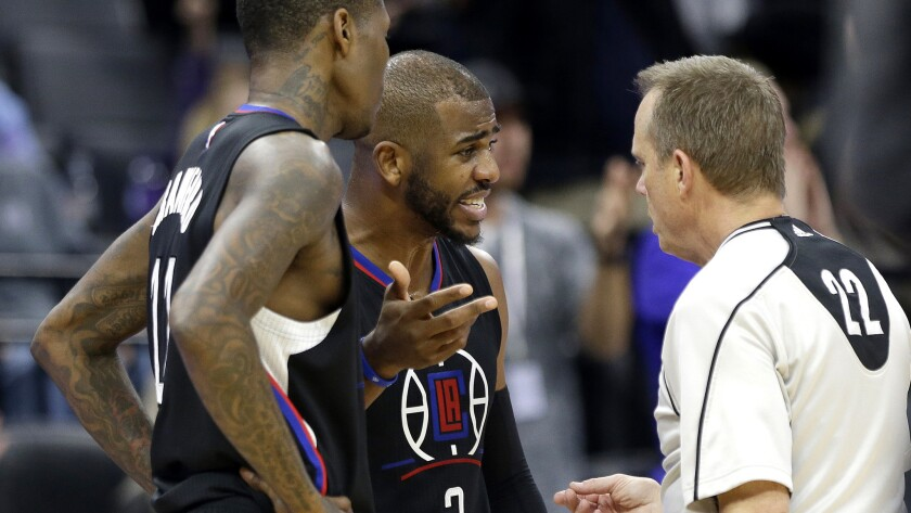 Clippers guards Chris Paul, center, and Jamal Crawford discuss a call with referee Bill Spooner during the second half against the Kings on Friday night in Sacramento.