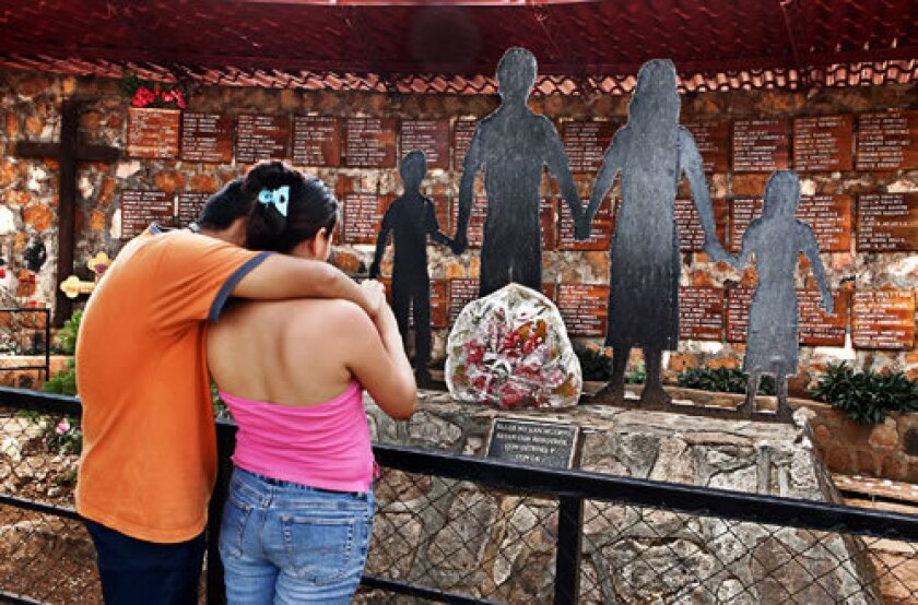Cristian Figueroa, 23, and his wife, Mariana Cunadas Figueroa, 26, embrace at the memorial in El Mozote, El Salvador, to the victims of the 1981 attack by an army unit in which up to 900 people were raped, tortured and massacred.