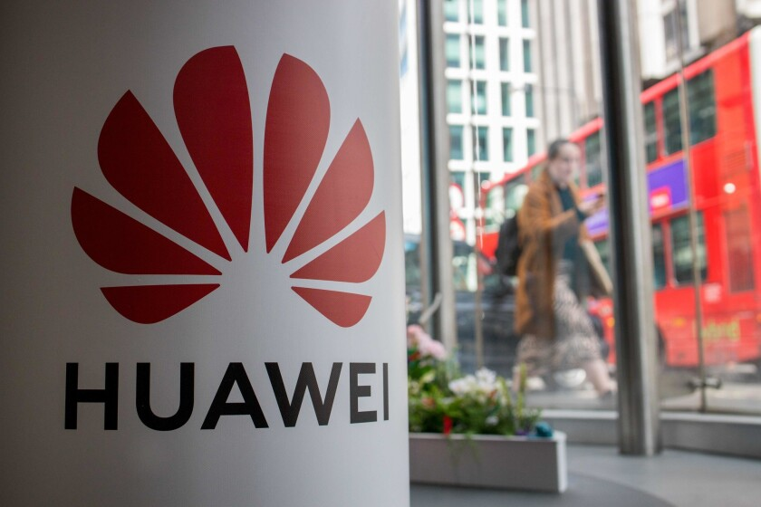 A pedestrian walks past a Huawei product stand at a telecommunications shop in central London.