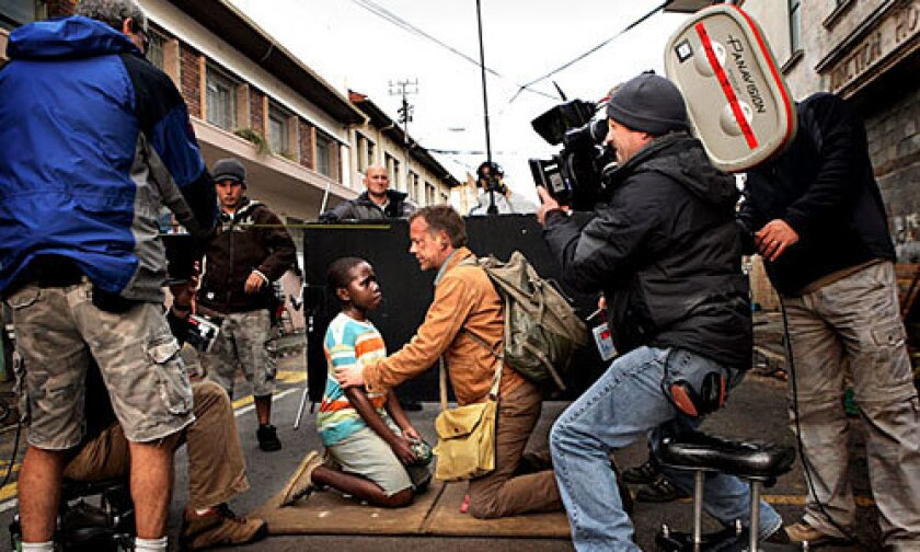 """A kneeling Kiefer Sutherland and Siyabulela Ramba prepare for a scene during the filming of """"24: Redemption"""" in Cape Town, South Africa. The two-hour special will air Nov. 23 on Fox as a precursor to the hit series' return in January for Season 7. The still photo here is included in an exhibit that opens Monday at the Paley Center for Media in Beverly Hills."""