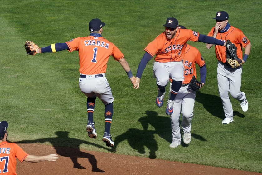 Houston Astros' Carlos Correa, left, and Houston Astros' George Springer, leap in celebration after they defeated the Minnesota Twins 3-1 in Game 2 to clinch the American League wild-card baseball series, Wednesday, Sept. 30, 2020, in Minneapolis. (AP Photo/Jim Mone)